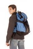 Zufälliger gekleideter junger Mann mit dem blauen Rucksack, der über shoulde schaut Lizenzfreies Stockbild