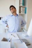 Zufälliger Geschäftsmann, der seinen schmerzend Rücken ausdehnt Stockfotografie