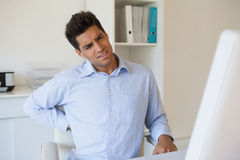 Zufälliger Geschäftsmann, der seinen schmerzend Rücken berührt Lizenzfreie Stockbilder
