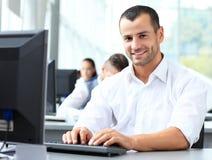 Zufälliger Geschäftsmann unter Verwendung des Laptops im Büro Stockbild