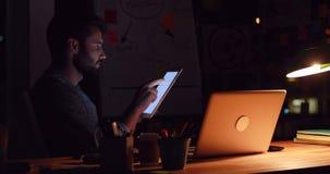 Zufälliger Geschäftsmann unter Verwendung einer Tablette nachts stock footage