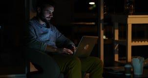 Zufälliger Geschäftsmann unter Verwendung eines Laptops nachts stock video footage