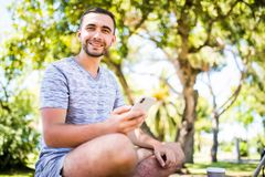 Zufälliger glücklicher Mann, der auf dem Smartphone sitzt auf einer Bank in einem Park schreibt stockfotografie