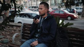 Zufälliger glücklicher Mann unter Verwendung des Smartphone, der auf einer Bank Gebrauchsspracherkennung ai-Sprachehelferaudio de stock video footage