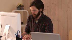 Zufälliger Hippie-Designer, der an einem Computer arbeitet stock footage