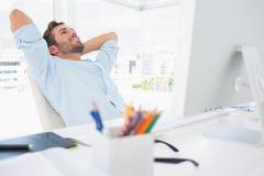 Zufälliger junger Mann, der bei den Händen hinter Kopf im Büro liegt Stockfotos