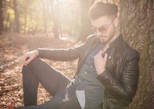 Zufälliger junger Mann, der im Park sitzt Stockfotografie