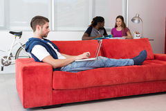 Zufälliger junger Mann, der Laptop auf Sofa verwendet Lizenzfreie Stockfotos
