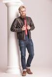 Zufälliger junger Mann, der seine Lederjacke repariert Lizenzfreie Stockfotografie