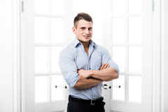 Zufälliger junger Mann des Porträts, der im Eingangsausgangsinnenraum auf dem hellen Hintergrund lächelt und schaut zur Kamera mi Lizenzfreies Stockbild