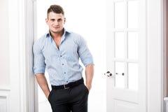 Zufälliger junger Mann des Porträts, der am Rahmen einer offenen Tür auf dem hellen Hintergrund lächelt und schaut zur Kamera sic Stockbild