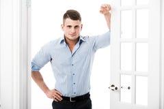 Zufälliger junger Mann des Porträts, der am Rahmen einer offenen Tür auf dem hellen Hintergrund lächelt und schaut zur Kamera sic Lizenzfreie Stockfotos