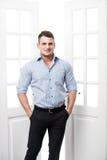 Zufälliger junger Mann des Porträts, der am Rahmen einer offenen Tür auf dem hellen Hintergrund lächelt und schaut zur Kamera sic Stockfotografie