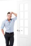 Zufälliger junger Mann des Porträts, der am Rahmen einer offenen Tür auf dem hellen Hintergrund lächelt und schaut zur Kamera sic Stockfoto