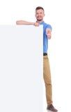 Zufälliger junger Mann mit Platte zeigt sich Daumen Stockfotos