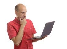 Zufälliger kahler Mann mit dem Laptopdenken Lizenzfreies Stockfoto