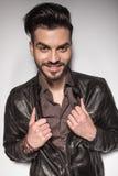Zufälliger lächelnder Mann beim Ziehen seiner Lederjacke Stockfotos