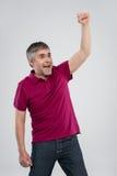 Zufälliger Mann, der über weißem Hintergrund gewinnt und feiert Stockfoto
