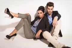 Zufälliger Mann, der auf dem Boden mit seiner Freundin sitzt Stockfotografie