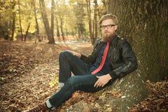 Zufälliger Mann, der eine Lederjacke, lehnend auf einem Baum trägt Stockbilder