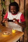 Zufälliger Mann, der Foto des Gebäcks und des Tasse Kaffees macht Stockbild