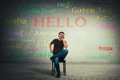 Zufälliger Mann gesetzt auf einem Stuhl, der am Handy spricht Glücklicher Manager, der verschiedene Sprachen mit seinen Kunden sp stockbild