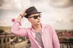 Zufälliger Mann mit der Sonnenbrille, die seinen Hut auf Kopf repariert Stockfoto