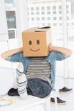 Zufälliger Mann mit glücklichem smileykasten über Gesicht im Büro Stockfotografie