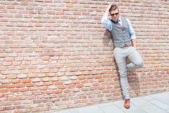 Zufälliger Mann steht gegen Backsteinmauer Stockfotografie