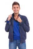 Zufälliger Mann zieht den Kragen und das Lächeln seiner Jacke Stockfoto