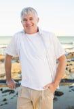 Zufälliger reifer Mann, der an der Kamera durch das Meer lächelt Stockfotos