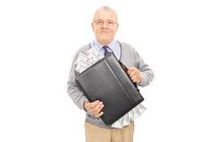 Zufälliger Senior, der einen Aktenkoffer voll vom Bargeld hält Lizenzfreies Stockfoto