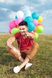 Zufälliger Sitzmann mit Ballonen zeigt auf Sie Stockfotografie