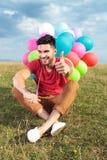Zufälliger Sitzmann mit Ballonen zeigt sich Daumen Lizenzfreie Stockfotografie