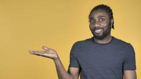 Zufälliges afrikanisches Mann-Vertretungs-Produkt an der Seite, gelber Hintergrund stock video