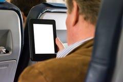 Zufälliges Geschäft Mann-Flugzeug-Seats, das leeres weißes Tablet E-R liest lizenzfreies stockbild