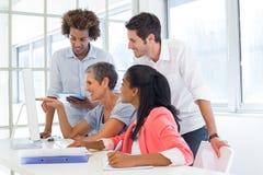 Zufälliges Geschäftsteam, das eine Sitzung mit Computer hat Lizenzfreie Stockbilder