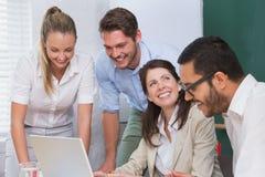 Zufälliges Geschäftsteam, das eine Sitzung unter Verwendung des Laptops hat Stockfotos