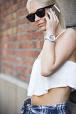 Zufälliges junges blondes Mädchen, das im Telefon spricht Stockfotografie