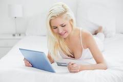 Zufälliges junges blondes tuendes on-line-Einkaufen im Bett Lizenzfreies Stockfoto