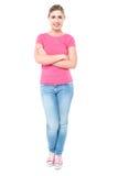 Zufälliges junges Mädchen, das, Arme gekreuzt aufwirft Stockfotos