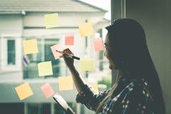 Zufälliges kreatives Geschäftsfrauschreibensideal und -ziel an zu den Fenstern Stockbild