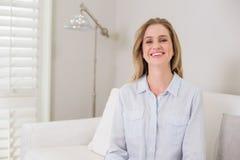 Zufälliges lachendes blondes Sitzen auf der Couch, die Kamera betrachtet Stockfotografie
