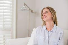 Zufälliges lachendes blondes Sitzen auf der Couch, die weg schaut Stockfotos