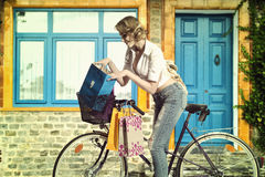 Zufälliges Mädchen mit byke und Einkaufstasche Stockbild