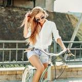 Zufälliges portait eines schönen Mädchens auf einem bycicle im Freien Stockfotos