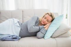 Zufälliges recht blondes Lügen auf dem Couchschlafen Lizenzfreie Stockbilder