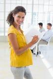 Zufälliges schwangeres Geschäftsfrauschreiben im Ordner, der an der Kamera lächelt stockfotos