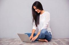Zufällige Frau, die auf dem Boden mit Laptop sitzt Stockfotos