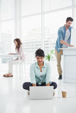 Zufällige Geschäftsfrau, die auf dem Boden unter Verwendung des Laptops sitzt Stockbilder